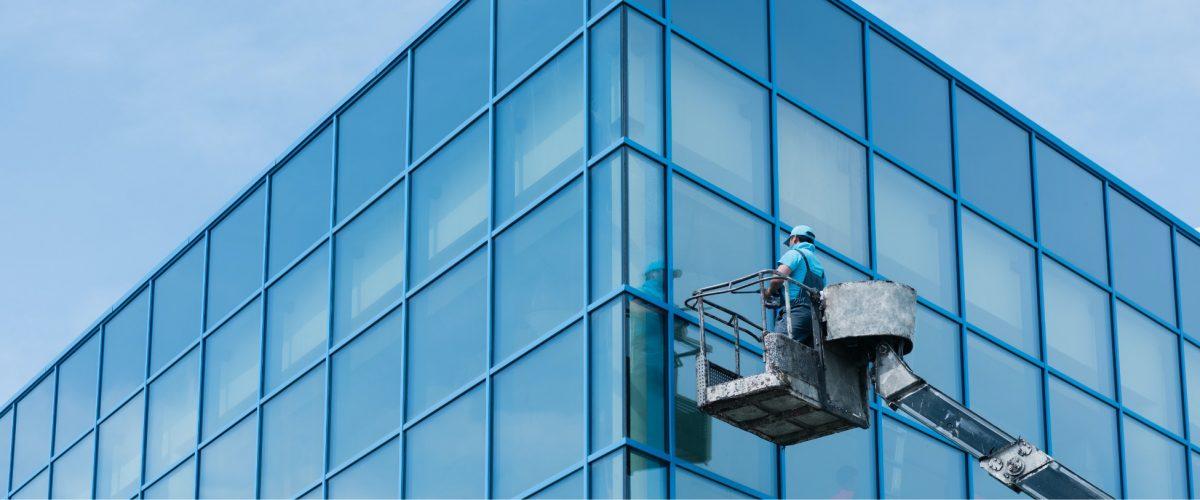 Fensterreiniger macht Fensterfront eines großen Bürogebäudes sauber