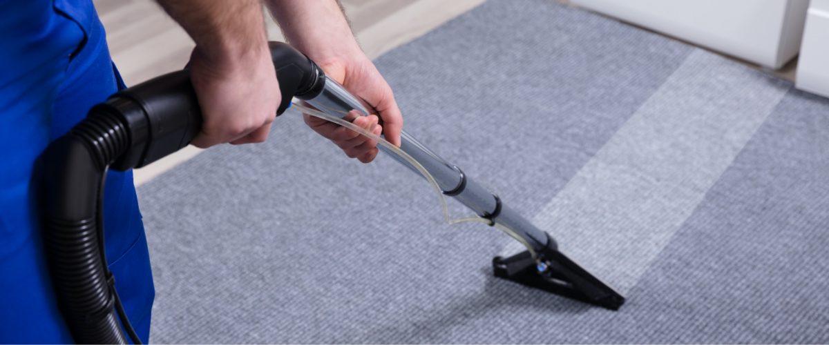Person reinigt Teppich mit Staubsauger